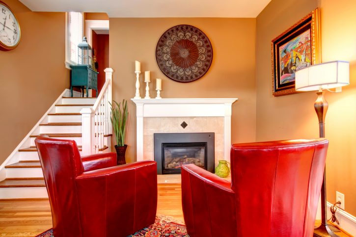 Living Room With Red Leather Armchairs In Front Of Fireplace And Wood Flooring