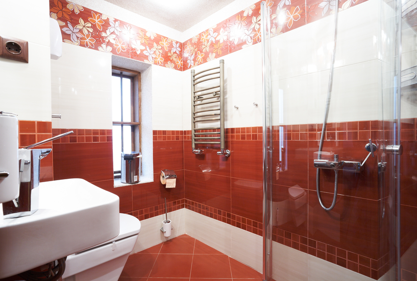Bathroom with red and white walls, red tile floor and white fixtures