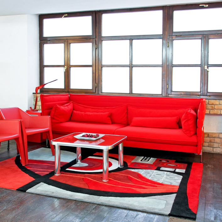 Loft apartment living room with white walls and red living room furniture