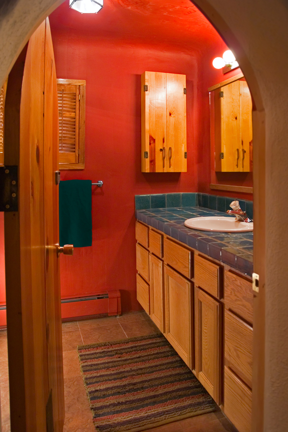 Wood bathroom with red wall and arched doorway and dark countertop