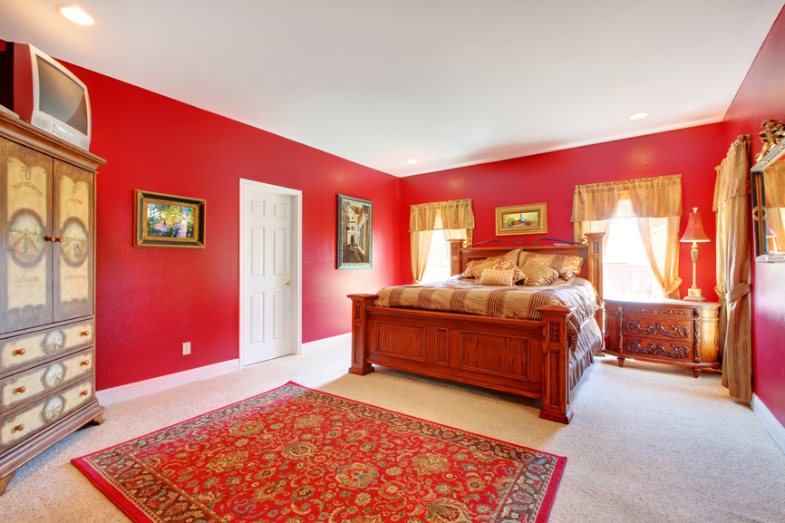 Master bedroom with red walls and white ceiling and large wood bed