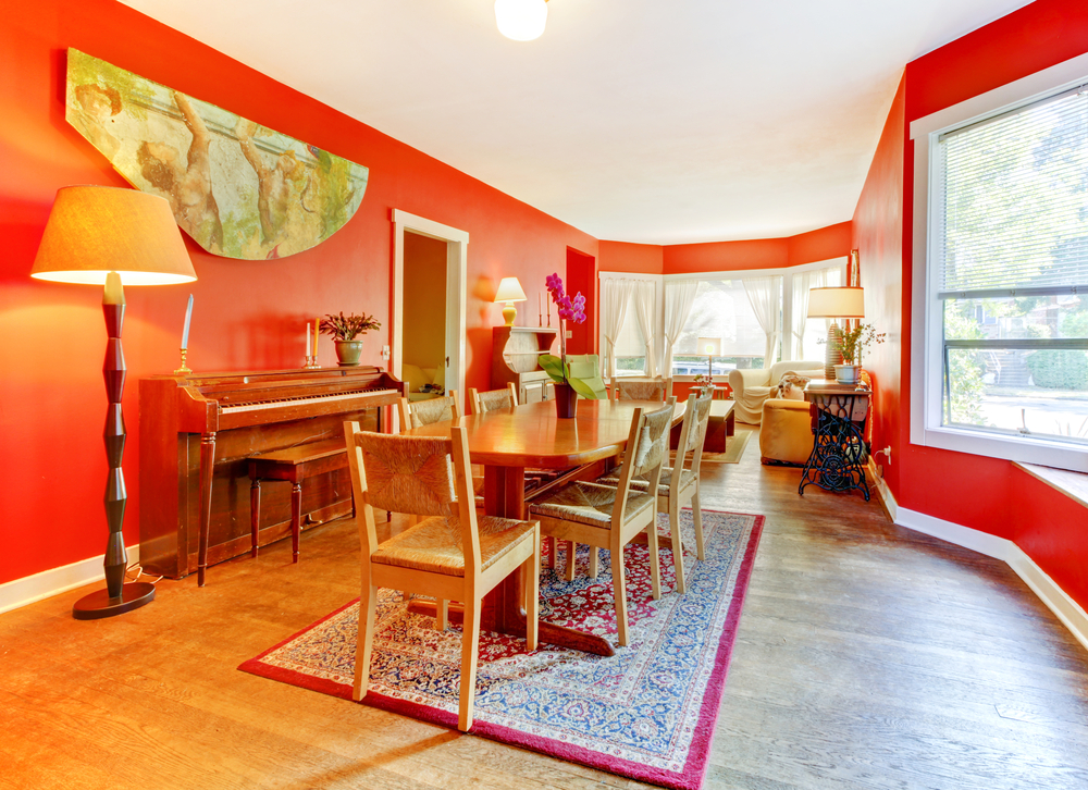 Family dining area with wood floor and red walls topped with white ceiling