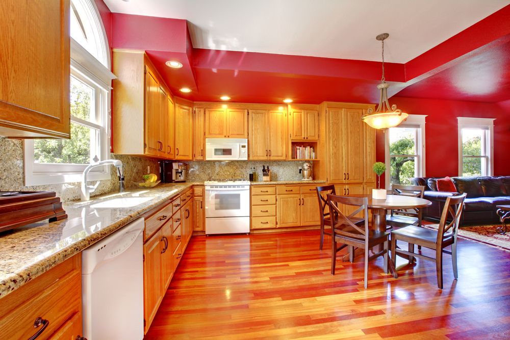 Large kitchen with wood floor and cabinets surrounded by red walls and topped with a white ceiling