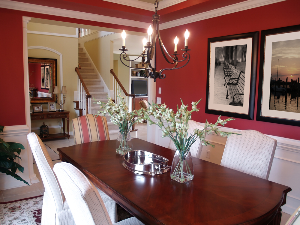 Formal dining room with white and red walls, dark wood table and white dining chairs