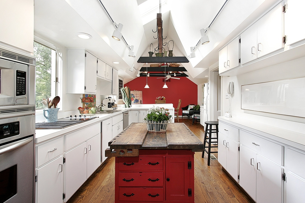 Large kitchen with cathedral ceiling, white cabinets and red island accented with one red wall