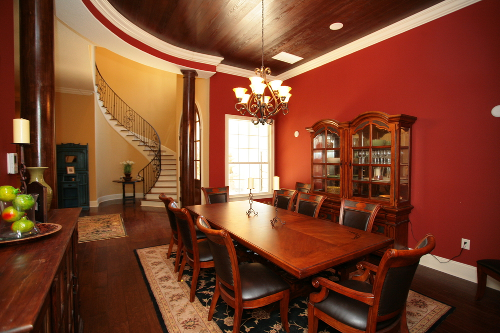Dining room with dark wood floor, wood dining set and one red wall