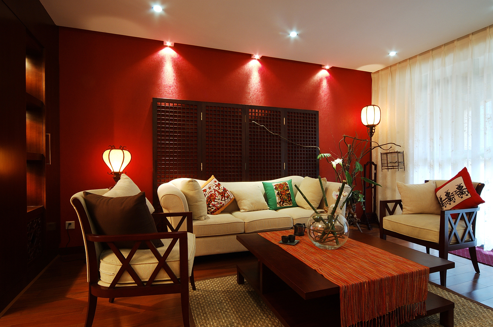 Living room with white furniture, wood coffee table, wood floor and one red  wall