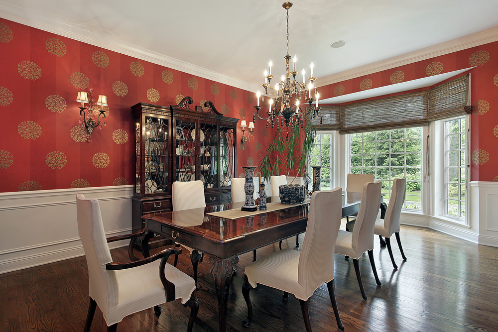 Formal dining room with red wallpaper, white dining chairs, dark wood dining table and bay window