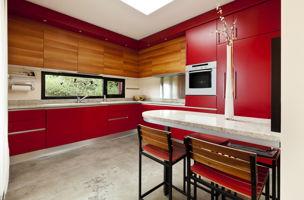 Kitchen with red and wood walls, red cabinets and white ceiling