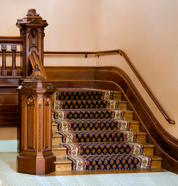 Ornate woodwork staircase with a patterned runner.