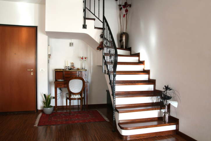 White riser with black balustrade and wooden tread staircase.