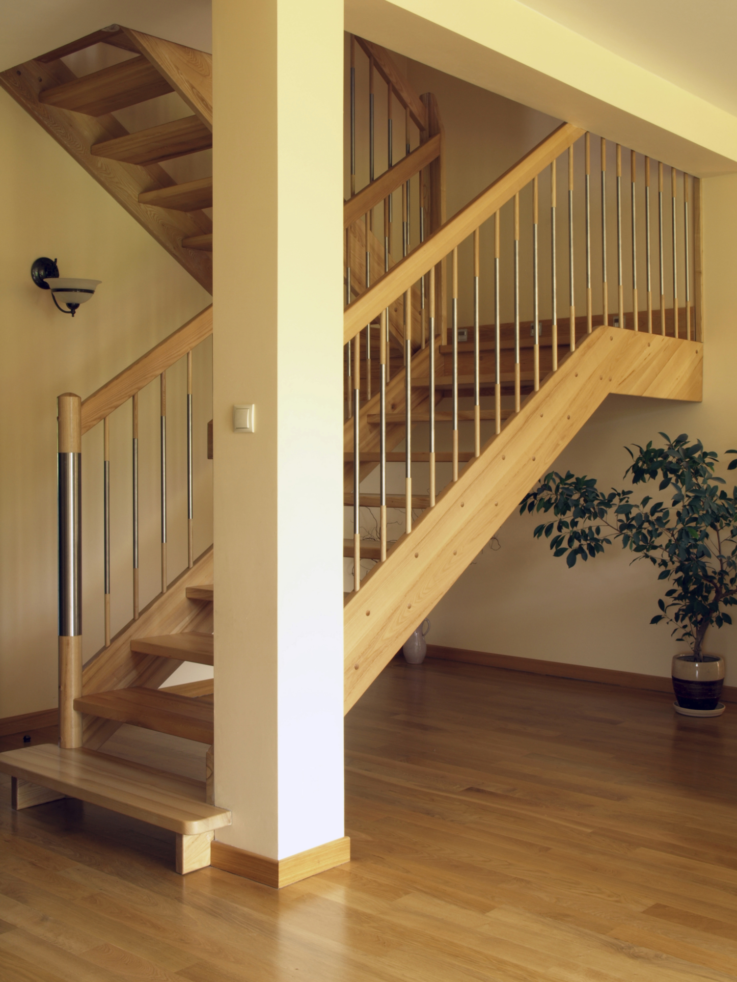 Wooden staircase with open risers and spindles wrapped in metal.