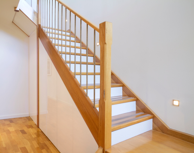Simple wooden stairs with white risers and metal spindles.