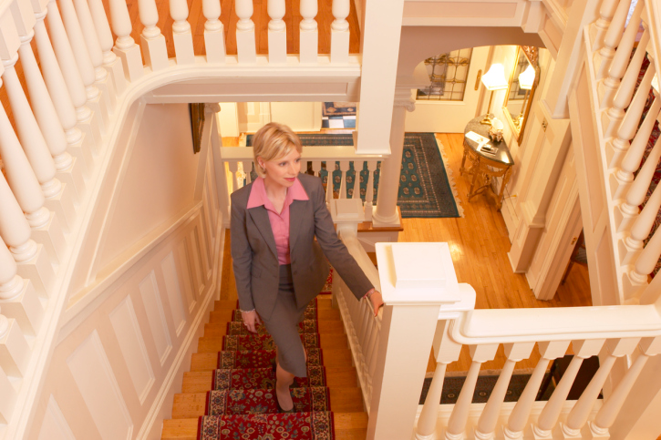 Traditional staircase with heavy spindles, oriental carpet like runner and wooden treads.