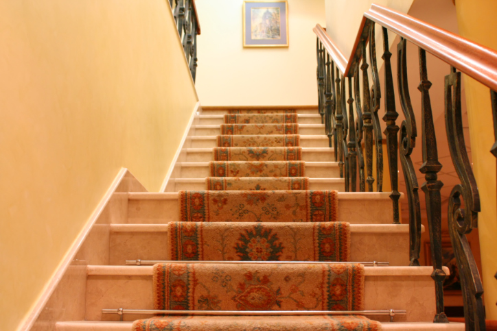 Staircase with ironwork balustrade and carpet runner.