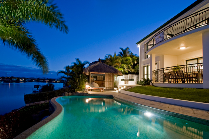 Waterfront pool at night in backyard of luxury Mediterranean style home