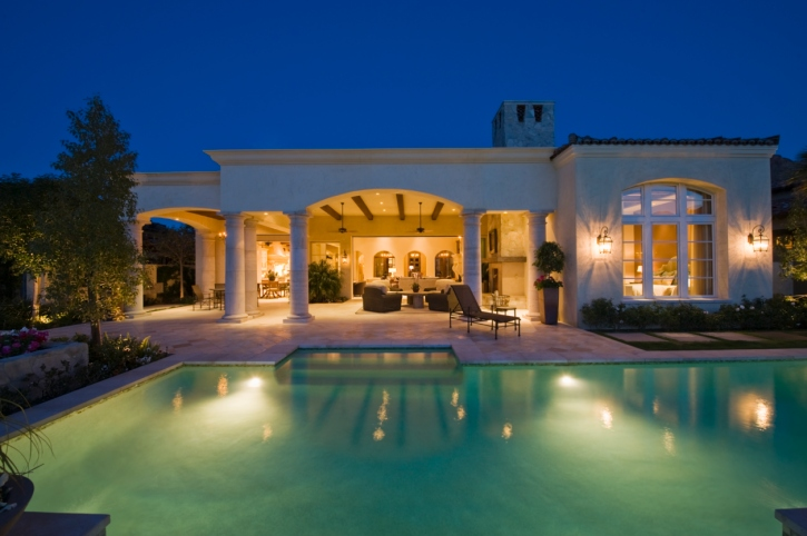 large pool in the backyard of a contemporary white mansion with covered patio