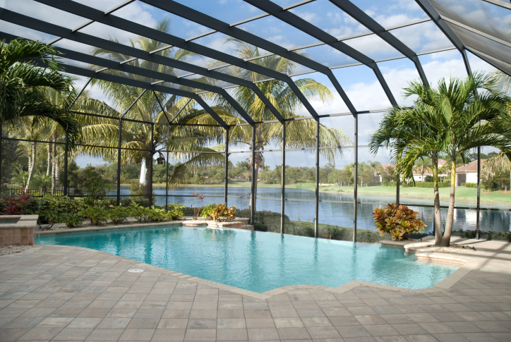 Screen Covered In Ground Pool In Florida Backyard Surrounded By Grey Brick  Patio