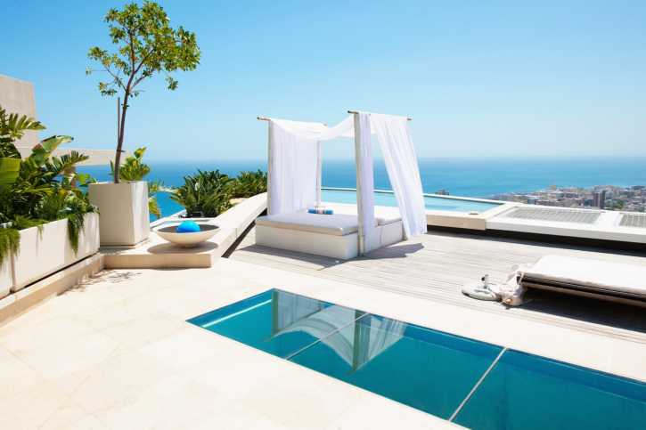 Small lap pool on white patio with a bed pergola overlooking the sea