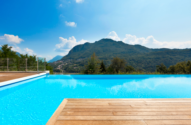 L-shaped light crystal blue pool with wood deck on edge of mountain forest
