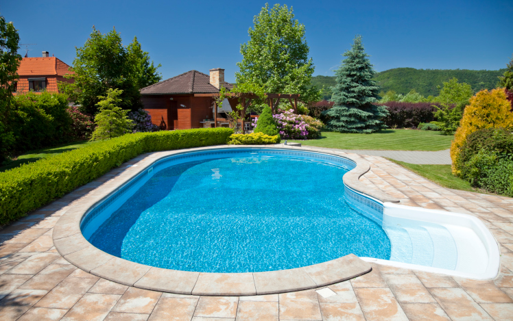 kidney shaped swimming pool with sanded brick patio and hedge