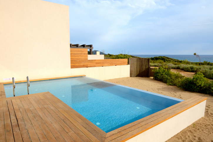 Small L-shaped dip pool with wooden deck on the beach