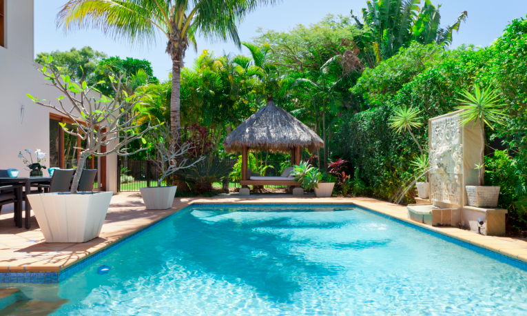 Large rectangle backyard pool with brick patio, thatch gazebo and large tropical hedge
