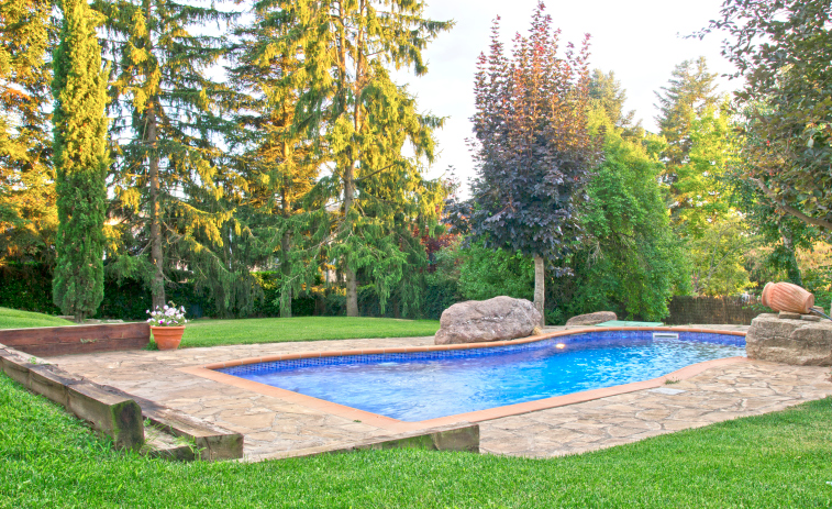 Stunning pool in the middle of the yard with brick patio and grass surrounding it