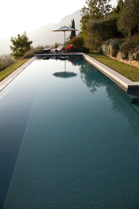 Elegant deep blue pool surrounded by grass patio