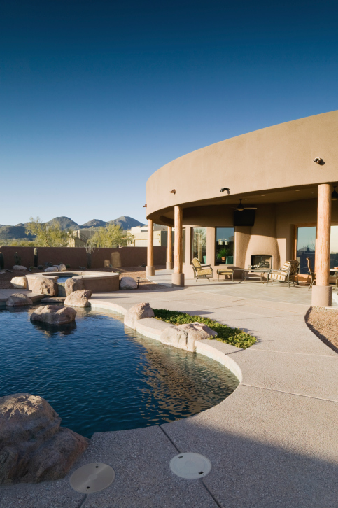 Desert-style one-story home with dark blue backyard pool surrounded by grey cement patio