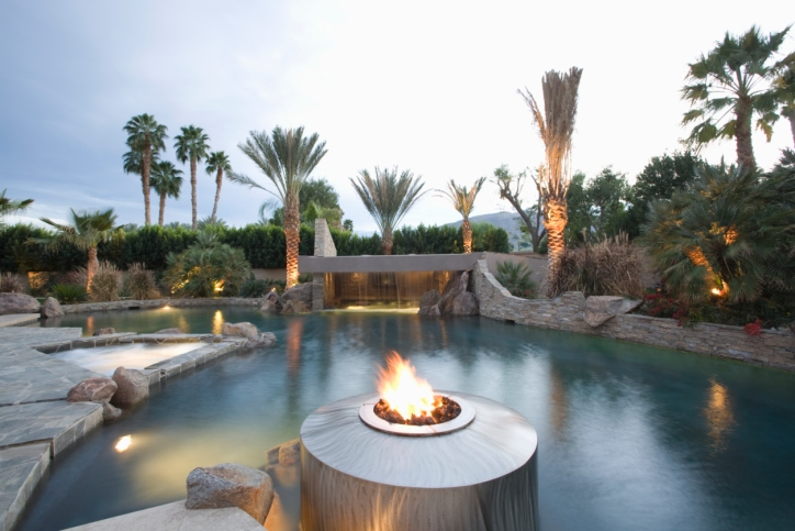 Huge swimming pool complex in backyard with stone patio, gas fire pit and palm trees