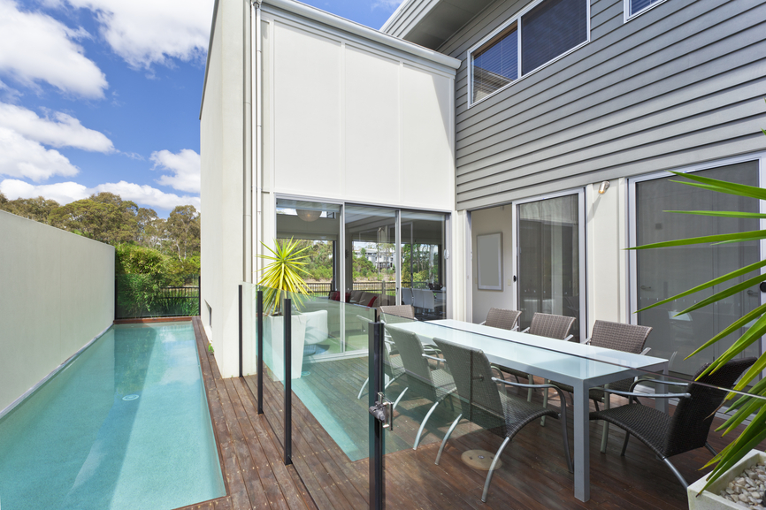 Home with small in-ground lap pool on the side bordered by dining deck