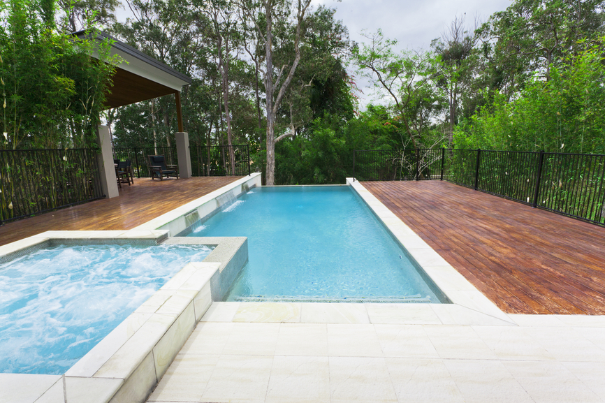Photo of backyard pool surrounded by red wood deck with hot tub over looking forest