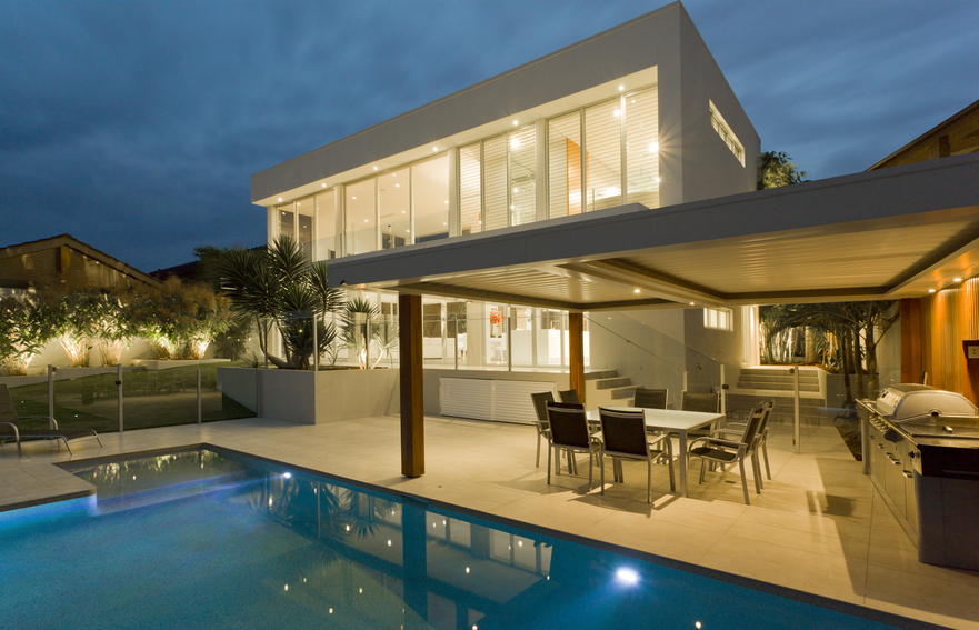 2 story modern home with small pool bordered by covered patio
