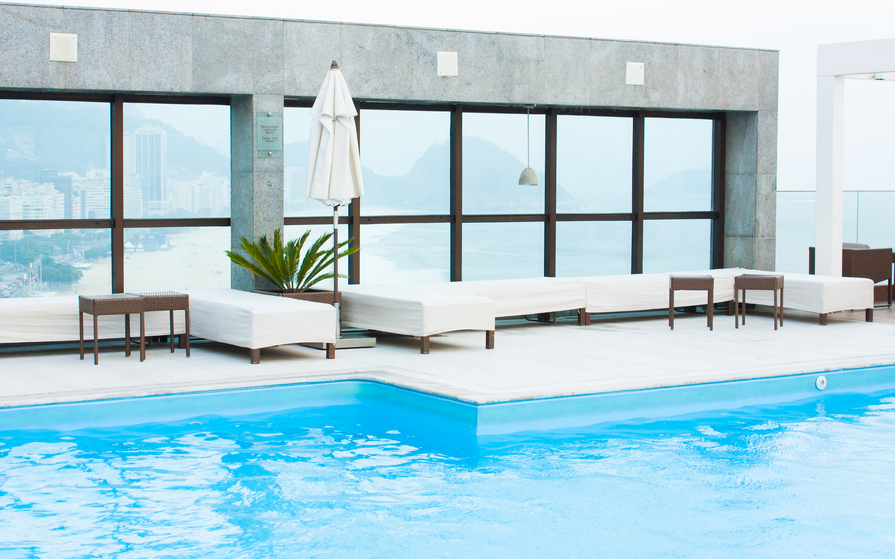 Modern home with light blue pool with wrap-around white patio and stylish modern white patio furniture