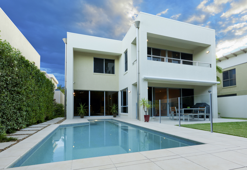 Modern two story home with rectangle swimming pool surrounded by grey stone patio and grass