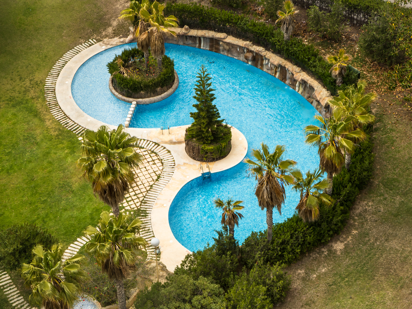Photograph of large kidney shape pool with tree islands - aerial view
