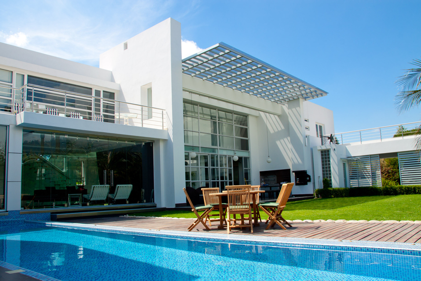 2-story white home with long rectangle pool bordered by wooden deck and grass
