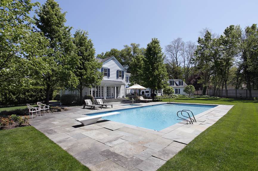 White colonial home with grey flagstone patio wrapped around in-ground pool with diving board