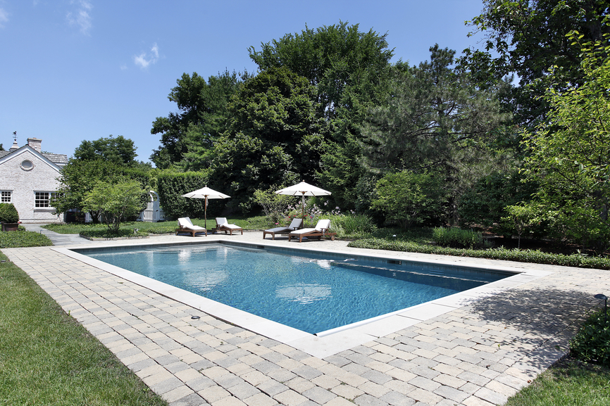 white colonial home with grey patio and trees surrounding pool