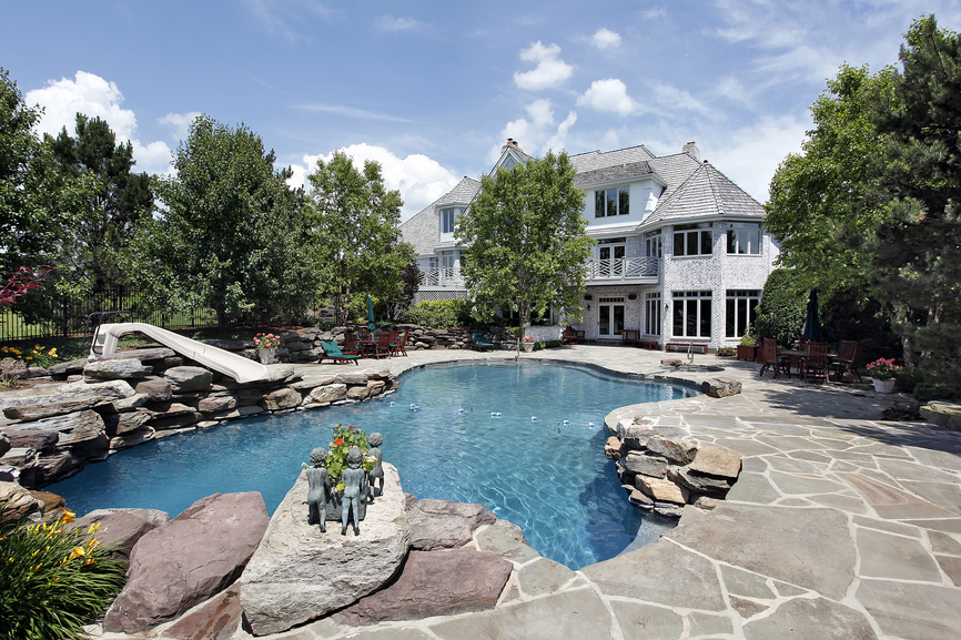3 story mansion with large pool surrounded by rocks with grey rock patio