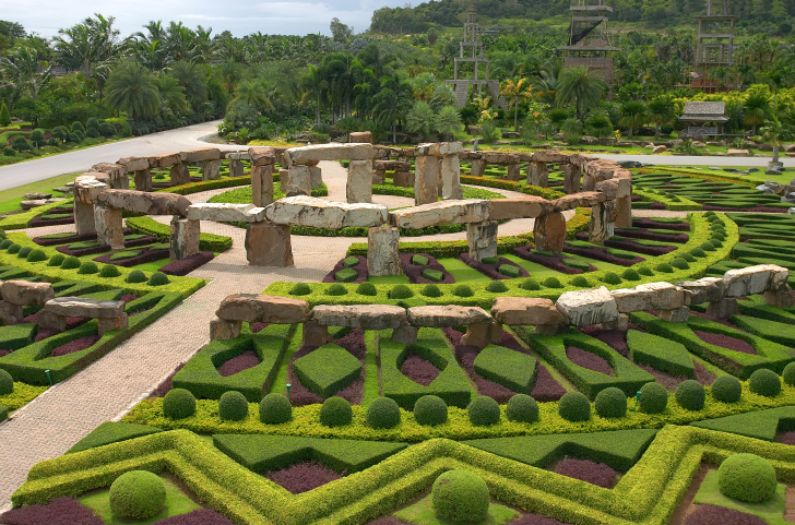 Extensive topiary gardens with many geometric shapes surrounding a rock sculpture