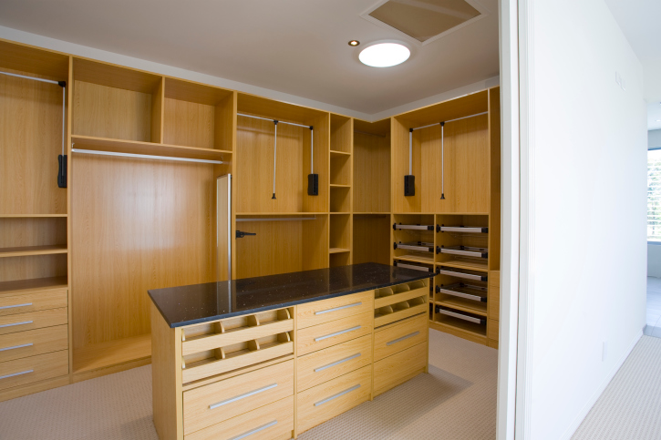 Light wood walk-in closet with large dresser island