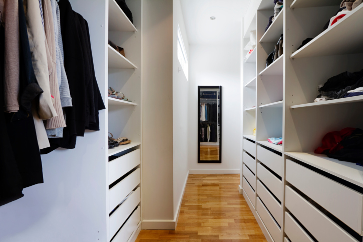 Long and narrow white walk-in closet with hard wood floor