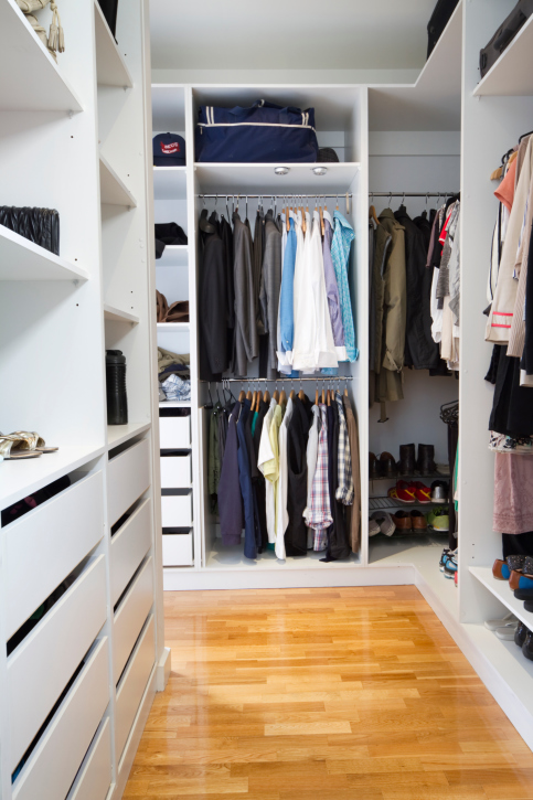 White walk-in wardrobe with light hard wood flooring