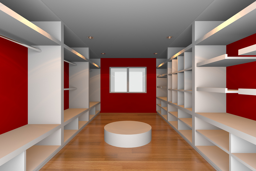 Dramatic and large walk-in closet with red walls, white shelving and hard wood flooring
