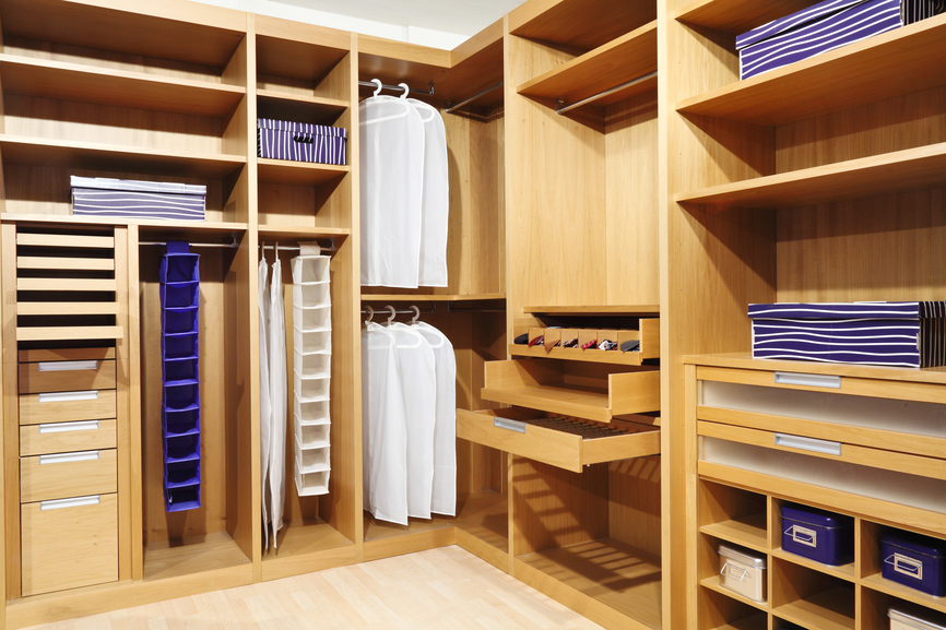 Nicely appointed walk in closet with pull out drawers and unique shelving