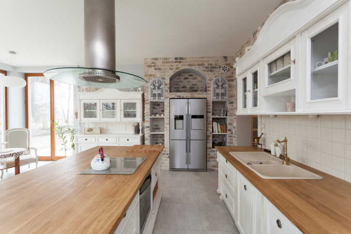 Large White Country Kitchen with Brick Wall and Wood Counter Tops