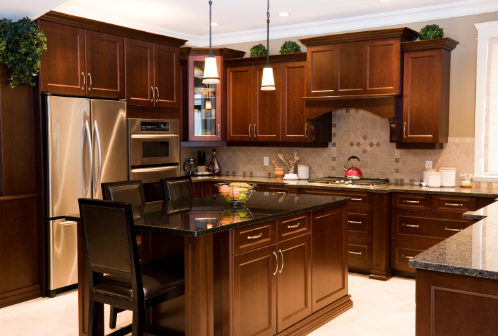 wood kitchen with black counter tops and stainless steel appliances