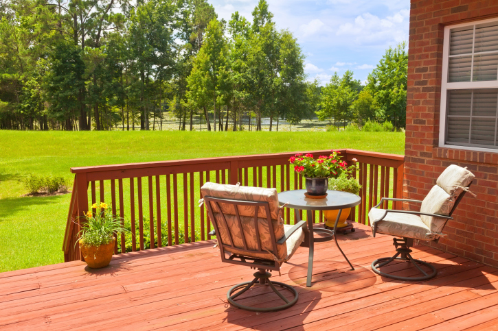 Simple redish wood deck with stairs to large grass yard